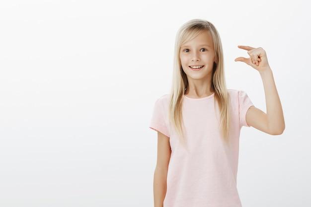 Menina sonhadora fascinada com cabelos loiros em uma camiseta rosa, modelando algo pequeno ou minúsculo com os dedos, maravilhada com o passarinho que ela viu no parque, parada surpresa sobre a parede cinza