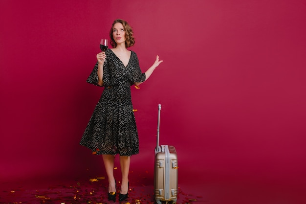 Menina sonhadora olhando para cima, segurando um copo de vinho ao lado da mala feita