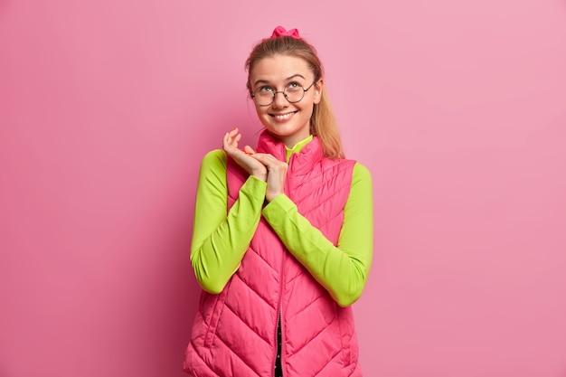 Menina sonhadora positiva com expressão alegre, maquina algo e esfrega as mãos, focada acima, usa óculos óticos, colete rosa, sorri agradavelmente, fica dentro de casa