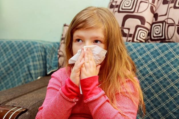 Menina sopra o nariz em um lenço de papel