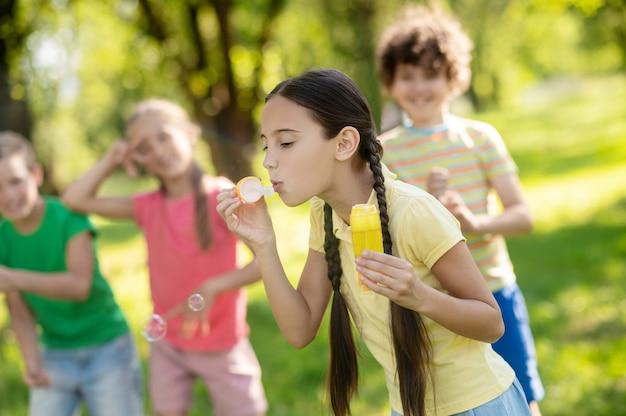 Menina soprando bolha de sabão e amigos