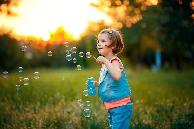 Menina, soprando bolhas de sabão ao ar livre