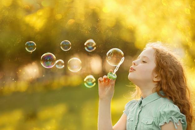 Menina, soprando bolhas de sabão na primavera ao ar livre.