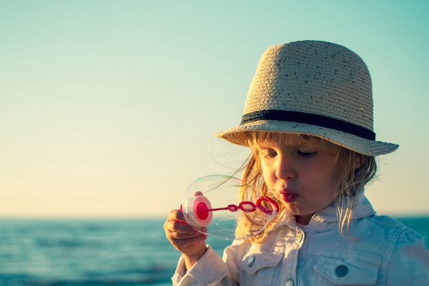 Menina, soprando bolhas de sabão no mar. foto tonificada
