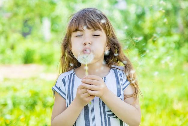 Menina, soprando dentes de leão no ar.