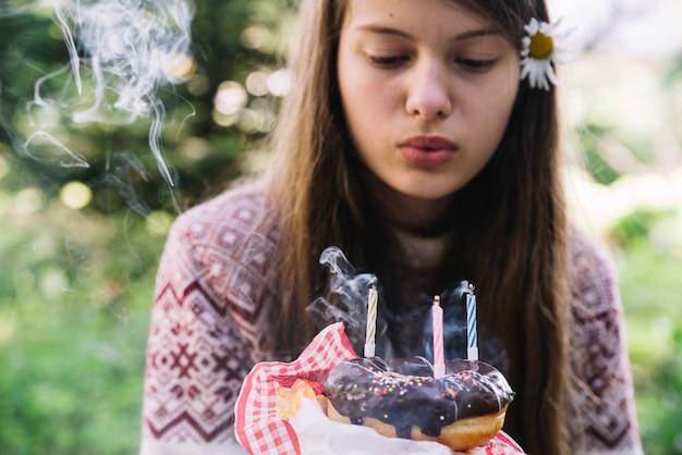 Menina soprando extinguir velas sobre o donut