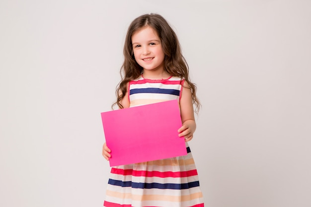 Menina sorri e segura um papel rosa vazio