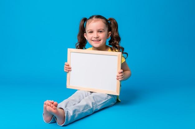 Menina sorri e segura uma prancheta vazia no azul