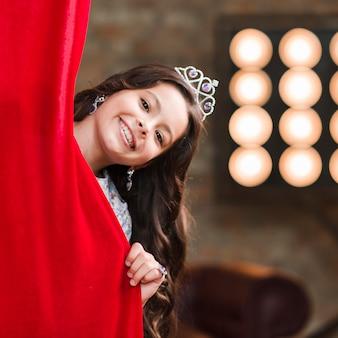 Menina sorridente, a espreitar por trás da cortina vermelha no backstage