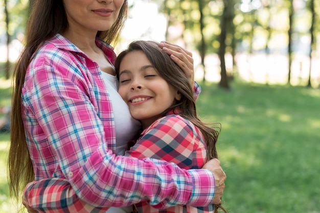 Menina sorridente, abraçando a mãe com os olhos fechados no jardim