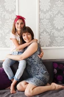 Menina sorridente, abraçando a mãe dela e olhando para a câmera enquanto está sentado no sofá