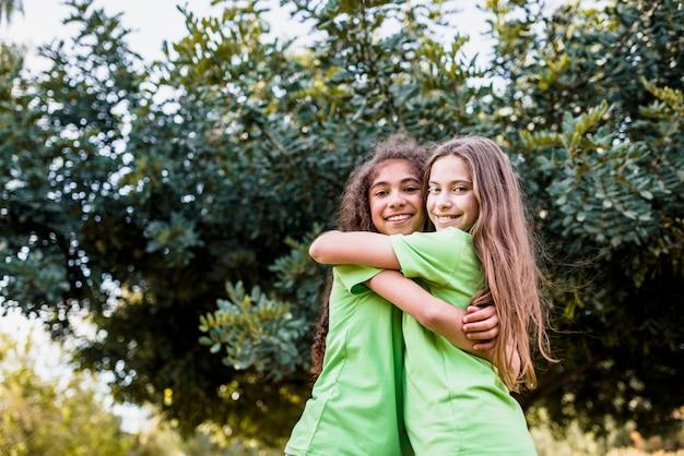 Menina sorridente, abraçando, um ao outro, contra, árvore verde