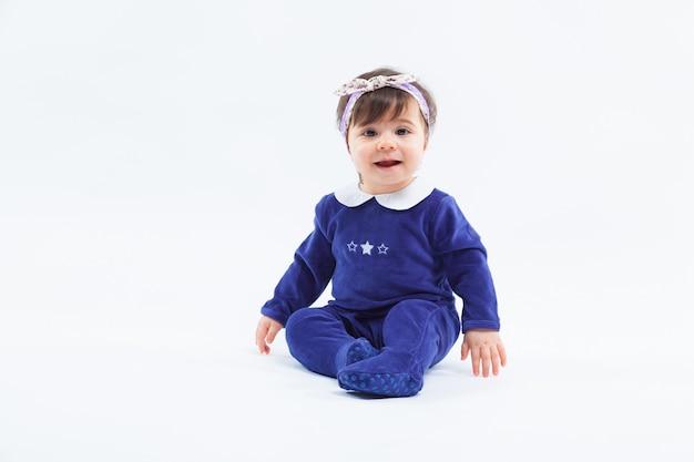 Menina sorridente adorável fofa com laço no cabelo, sentado no estúdio posando em branco