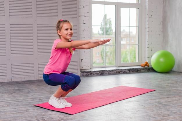 Menina sorridente, agachando-se e exercitando-se no tapete rosa