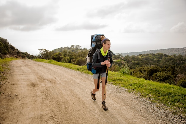 Menina sorridente, andando no caminho verde com mochila para caminhadas