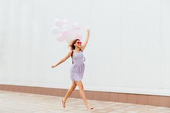Menina sorridente animada em óculos de sol rosa correndo com balões, usando vestido e sandálias