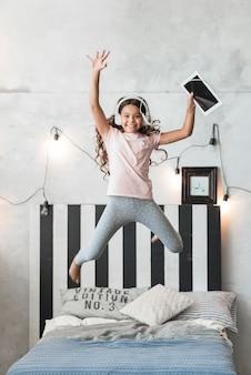 Menina sorridente animada pulando na cama com fone de ouvido e tablet digital