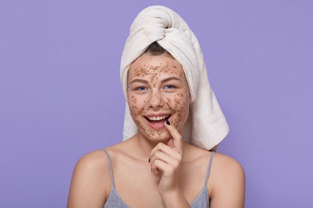 Menina sorridente, aplicar a máscara de café ou esfoliação na pele, olha para a câmera, usando toalha, fazendo manipulação de tratamento de beleza