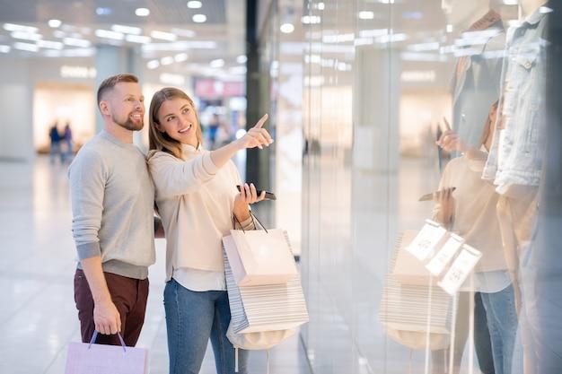 Menina sorridente apontando para uma das jaquetas dos manequins na vitrine da loja enquanto mostra ao namorado que tipo de roupa casual ela gosta