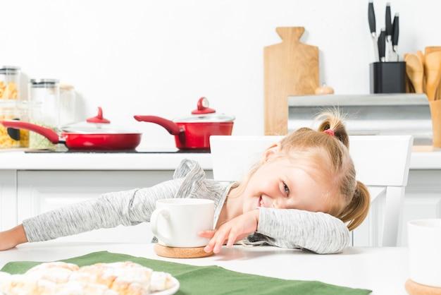Menina sorridente bonitinha com branca xícara de chá e café da manhã