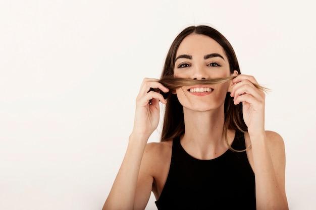 Menina sorridente brincando com o cabelo