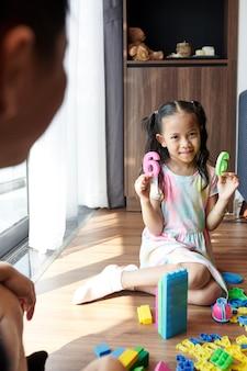 Menina sorridente, brincando com o pai, mostrando o plástico número seis e olhando para a câmera