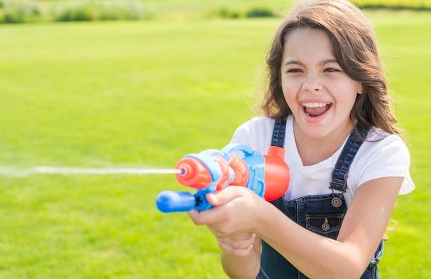 Menina sorridente brincando com pistola de água