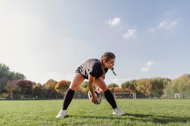 Menina sorridente, brincando com uma bola de rugby