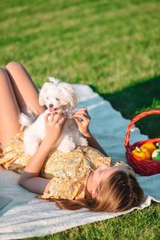 Menina sorridente brincando e abraçando o cachorrinho no parque