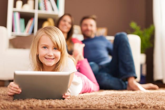 Menina sorridente brincando no tablet e deitada no tapete