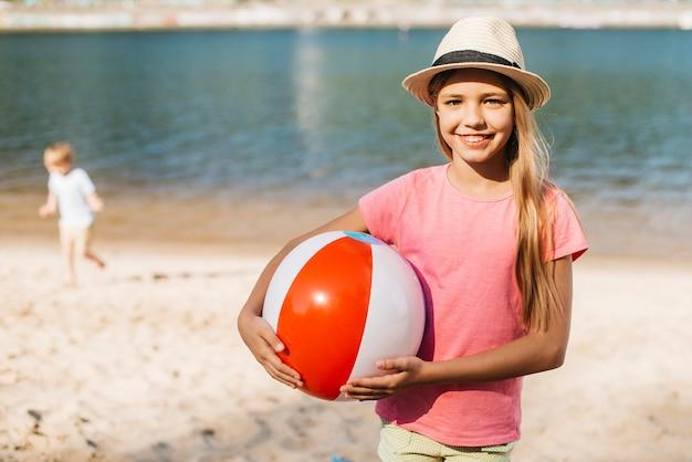 Menina sorridente carregando bola de praia ambas as mãos