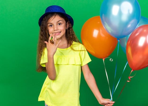 Menina sorridente caucasiana com chapéu de festa azul segurando balões de hélio e apito de festa isolado na parede verde com espaço de cópia