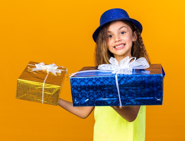 Menina sorridente caucasiana com chapéu de festa azul segurando caixas de presente isoladas na parede laranja com espaço de cópia