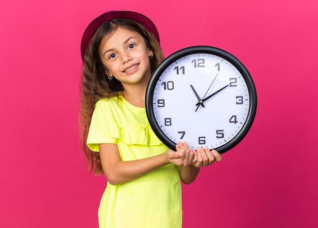 Menina sorridente caucasiana com chapéu de festa roxo segurando um relógio isolado na parede rosa com espaço de cópia