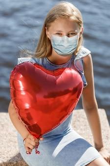 Menina sorridente com balão de coração em uma máscara médica no rosto