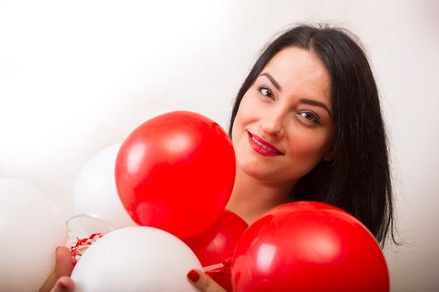Menina sorridente com balões de bolas vermelhas e brancas