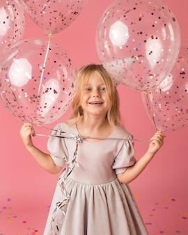 Menina sorridente com balões fantasiados