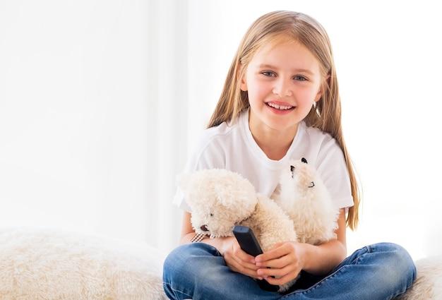 Menina sorridente com brinquedos na sala iluminada