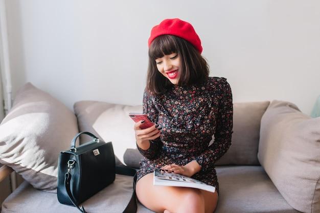 Menina sorridente com cabelo castanho na boina francesa da moda e vestido curto vintage escrever mensagem para um amigo. retrato de uma jovem morena atraente, descansando no sofá e lendo uma revista de moda