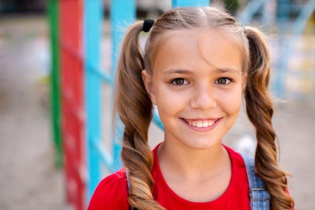 Menina sorridente com cabelos loiros, olhando para a câmera