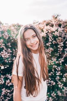 Menina sorridente com cabelos longos, olhando para a câmera
