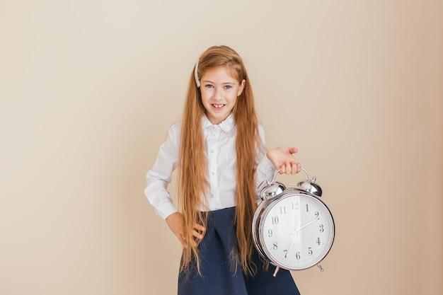 Menina sorridente com cabelos longos, segurando o grande relógio em fundo neutro. gerenciamento de tempo, prazo, hora de estudar, conceito de escola