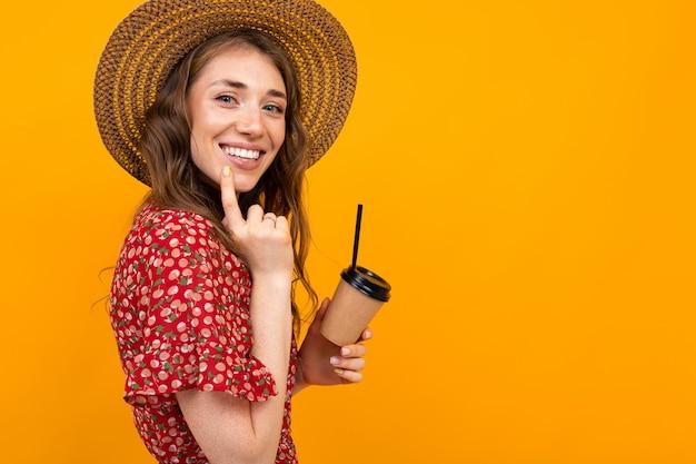 Menina sorridente com café em um amarelo em um vestido vermelho