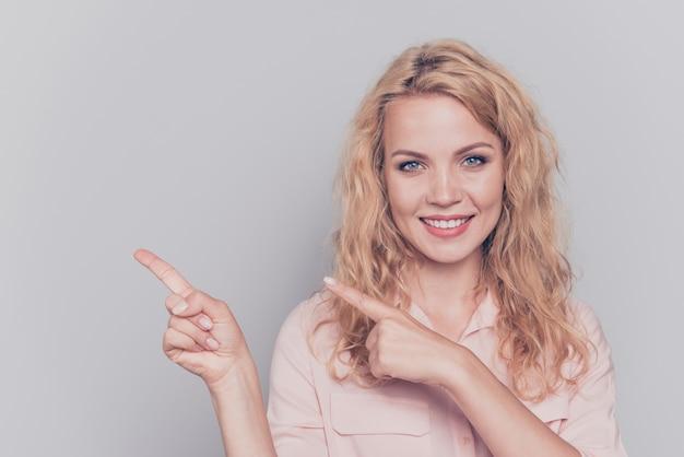 Menina sorridente com camisa apontando os dedos
