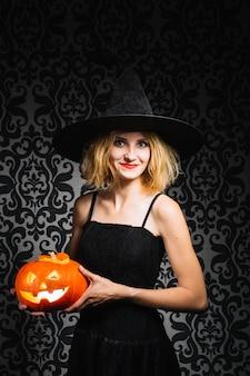 Menina sorridente com chapéu de bruxa com abóbora