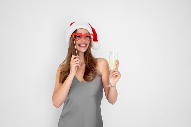 Menina sorridente com chapéu de papai noel e óculos de mentira segurando taça de champanhe na festa de ano novo
