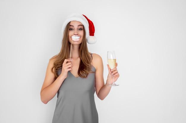 Menina sorridente com chapéu de papai noel e sorriso fingido segurando taça de champanhe na festa de ano novo