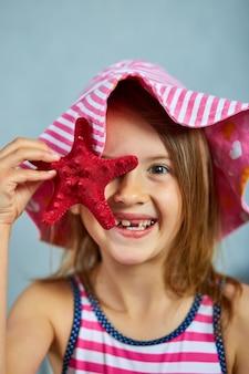 Menina sorridente com chapéu rosa segurando estrela do mar. conceito de férias de verão com close-up retrato do rosto de menina bonita.