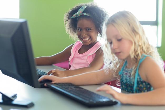 Menina sorridente com colega usando computadores