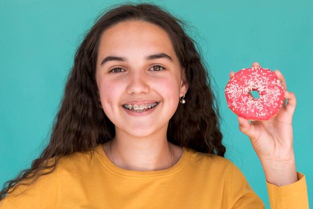 Menina sorridente com donut de vidro